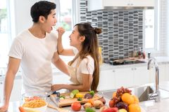 Couple together in kitchen room, Young asian woman holding vegetables to man royalty free stock photos