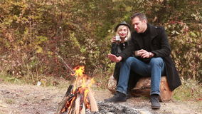 Couple together near fire drinking tea. Girlfriend and boyfriend together near fire drinking tea stock video