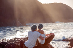 Couple together on the rocky coast. Romantic couple dressed in white embracing on the rocky ocean coast with mountain silhouette on the sunset Royalty Free Stock Images