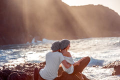 Couple together on the rocky coast. Romantic couple dressed in white embracing on the rocky ocean coast with mountain silhouette on the sunset Royalty Free Stock Photos