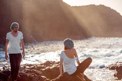 Couple together on the rocky coast. Romantic couple dressed in white enjoying on the rocky ocean coast with mountain silhouette on the sunset Stock Image