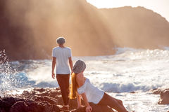 Couple together on the rocky coast. Romantic couple dressed in white enjoying on the rocky ocean coast with mountain silhouette on the sunset Royalty Free Stock Images