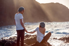 Couple together on the rocky coast. Romantic couple dressed in white holding hands on the rocky ocean coast with mountain silhouette on the sunset Royalty Free Stock Photos