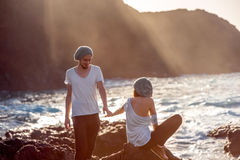 Couple together on the rocky coast Stock Photography