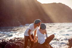 Couple together on the rocky coast. Romantic couple dressed in white holding hands on the rocky ocean coast with mountain silhouette on the sunset Royalty Free Stock Image