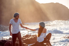 Couple together on the rocky coast. Romantic couple dressed in white holding hands on the rocky ocean coast with mountain silhouette on the sunset Stock Photography