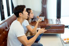 Couple together watching television in room. Couple together watching television serious reaction on sofa in living room at room Stock Image