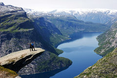 Couple on tongue of troll. Young couple on tongue of troll, norwey panoramic Stock Images
