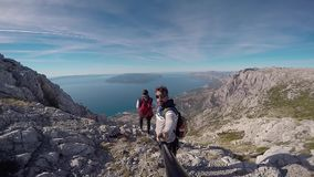 Couple on top of mountain. With GoPro camera. Panoramic view of sea horizon stock video