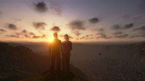Couple on top of the mountain, time lapse sunrise, tilt up stock video