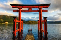 Couple at Torii gate of Hakone. Japanese couple at red Torii gate of Hakone shrine located on lake Ashi, Japan. Gateways entrance to Shinto shrines and famous Stock Photography