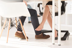 Couple touching each other under the table Stock Images