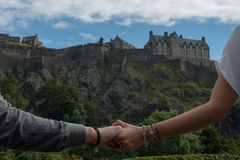 Couple touching hands with Edinburgh Castle as a Background. Couple traveling touching hands with Edinburgh Castle as a Background landscape Royalty Free Stock Images