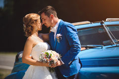 Couple Touching by Noses. Bride and groom touching by noses by blue car Royalty Free Stock Images