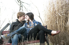 Couple Touching Noses On Park Bench. Young couple on a park bench looking at each other and touching noses Royalty Free Stock Photo