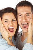 Closeup of happy young couple screaming. Couple touching their faces while shouting Stock Photo
