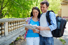 Couple on tour. Portrait of travelers studying map of ancient town Royalty Free Stock Images