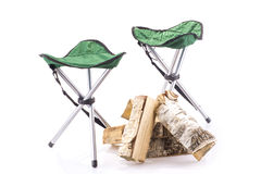 Couple of tourist chairs and firewood Stock Photos