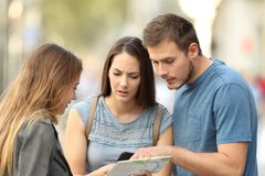 Couple of tourists asking for help on the street. Couple of three worried tourists asking for help to a girl on the street stock photography