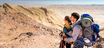 Couple tourists backpackers standing desert mountain peak ridge. Royalty Free Stock Images