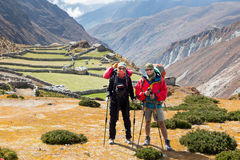 Couple tourists backpackers standing mountain farm village, Nep. Couple people tourists backpackers mountaineers standing above mountain canyon, farm village stock image