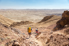 Couple tourists backpackers walking descending  desert stone mou Royalty Free Stock Image