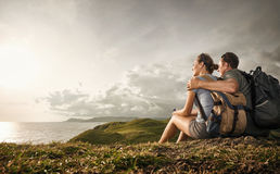 Couple tourists with backpacks enjoying sunset on top of a mount. Hikers with backpacks relaxing on top of a hill and enjoying view of sunset in ocean. Island Royalty Free Stock Photos