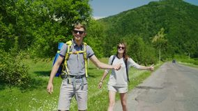 A couple of tourists with backpacks hitchhiking on the road, catch a passing car. Travel and adventure concept. 4K video stock video footage