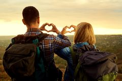A couple of tourists with backpacks made a symbol of the heart w Royalty Free Stock Photography