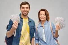Couple of tourists with backpacks and money. Travel, tourism and vacation concept - happy couple of tourists with backpacks and money over grey background stock images