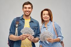 Couple of tourists with backpacks and money. Travel, tourism and vacation concept - happy couple of tourists with backpacks and money over grey background royalty free stock photo
