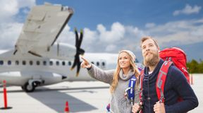 Couple of tourists with backpacks over plane stock photos
