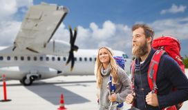 Couple of tourists with backpacks over plane stock photo