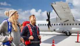 Couple of tourists with backpacks over plane royalty free stock photos
