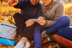 Couple of tourists with backpacks searching for right way using navigator in autumn forest. Women having rest. Couple of tourists with backpacks searching for royalty free stock photos