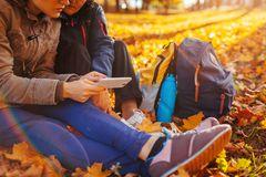 Couple of tourists with backpacks searching for right way using navigator in autumn forest. Women having rest. Couple of tourists with backpacks searching for stock photo