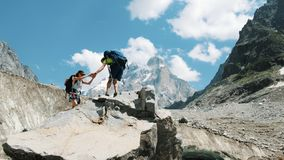 Couple of tourists with backpacks in the trek climb to the top of the stone and kiss. stock image
