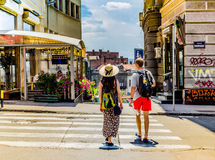A couple of Tourists in Belgrade, Serbia in July 2014. A young girl in a dress with a big hat and a man in red shorts with backpacks travelling in summer looking Royalty Free Stock Photos