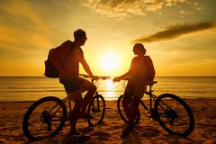 Couple tourists with Bicycles Watching Sunset. Silhouette people Stock Photos