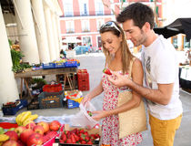 Couple of tourists buying fruits in local street market royalty free stock photo