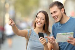 Couple of tourists checking location on the street. Couple of tourists checking location in a smart phone and paper map standing on the street Royalty Free Stock Image