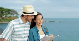 Couple of tourists checking map on the beach stock video footage