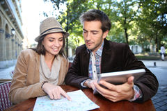 Couple of tourists checking on map touristic monuments Stock Image