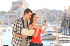 Couple of tourists checking online information on vacation. Happy couple of tourists checking online information in a smart phone on vacation Royalty Free Stock Photo