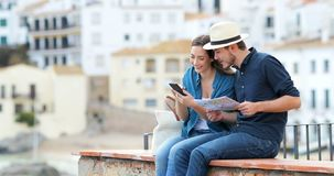 Couple of tourists comparing phone and paper map stock footage