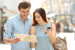 Couple of tourists consulting a city guide and mobile gps. Couple of tourists consulting a city guide and mobile phone gps in a street Stock Photos