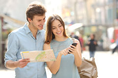 Couple of tourists consulting a city guide and smartphone gps. In the street searching locations Royalty Free Stock Photography