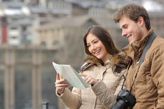 Couple of tourists consulting a guide in winter Royalty Free Stock Photos