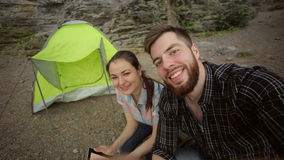 Couple of tourists doing a selfie near the tent. stock video