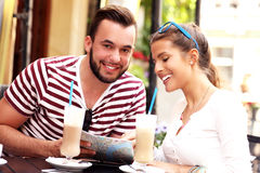 Couple of tourists drinking frappe in a cafe Stock Images